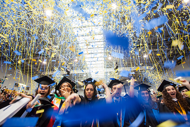 Group of Pace University graduates cheering at their Commencement ceremony